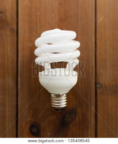 recycling, electricity, environment and ecology concept - close up of energy saving lighting bulb on wooden boards