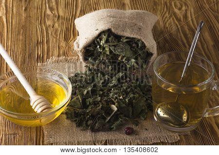 fresh herbal tea and honey on wooden desk