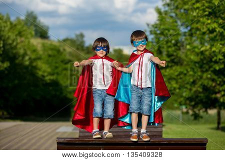 Two Sweet Little Preschool Children, Boys, Playing Superhero In The Park