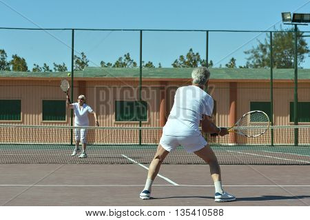 Portrait of active senior couple on tennis court