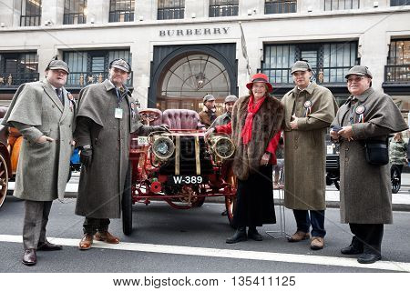LONDON - OCTOBER 31: Participants in the annual London to Brighton veteran car run pose in front of their car dressed in period garb at the Regent Street classic car show on October 31, 2015 in London
