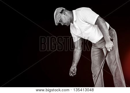 Golf player picking up golf ball against black background