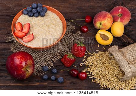 Breakfast with porridge strawberry apple cherry blueberry and apricots on a wooden table