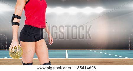 Female athlete with elbow pad holding handball against digital image of handball field indoor