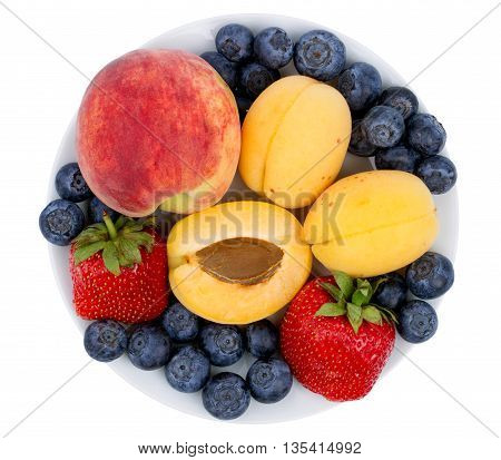 Fresh blueberry strawberry peach and apricot on a white plate isolated on a white background