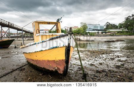 Old fishing boat is moored on beach at low tide in Santa Cruz island Oleiros Rias Altas A Coruna Spain.
