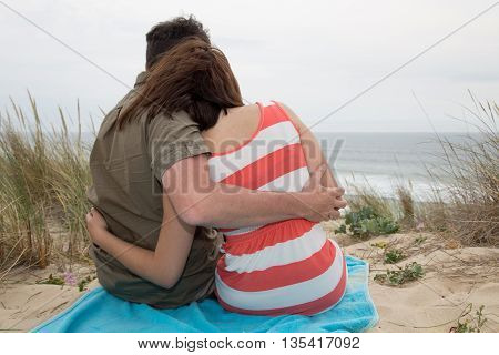 Back View Of Couple Sitting On A Beach Springtime