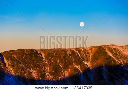 Morning View of Mountain Snowbound Ridge with Full Moon on Blue Sky