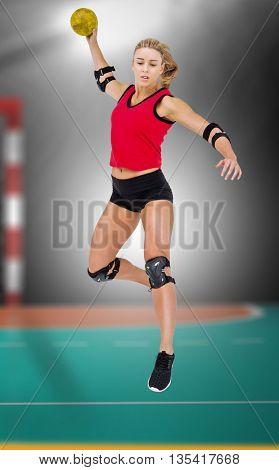 Female athlete with elbow pad throwing handball against handball field indoor