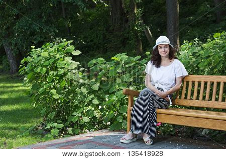 Girl sits on a bench in a city park. Girl rests in the shade of trees on the bench.