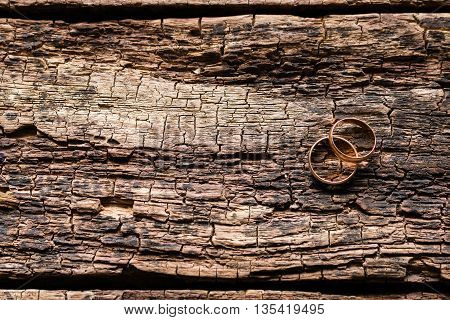 two gold rings on a wooden background