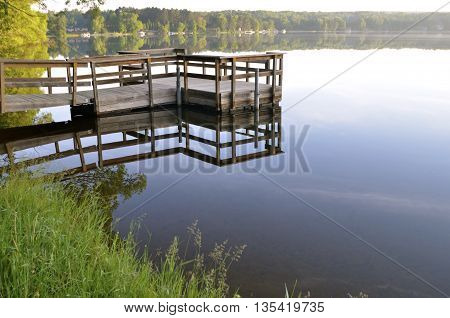 A dock extending over the water casts it  reflection upon the smooth tranquil water of a lake