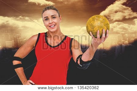 Female athlete with elbow pad holding handball against aerial view of a city on a cloudy day