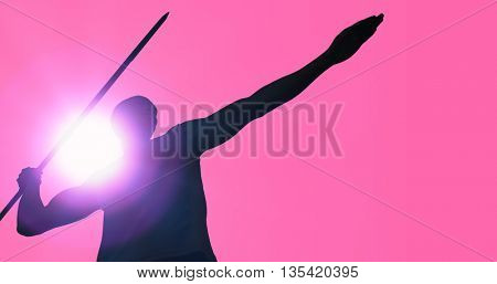 Low angle view of sportsman practising javelin throw against pink background