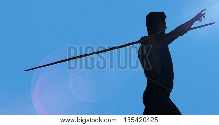 Rear view of sportsman practising javelin throw against blue background