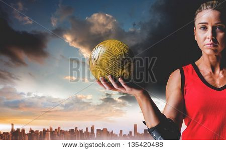 Female athlete with elbow pad holding handball against city on the horizon