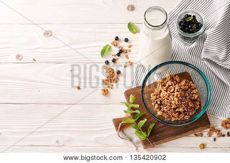 A food background with a glass bowl of cereal breakfast, milk or yogurt bottle and striped table cloth. Wooden background, top view.
