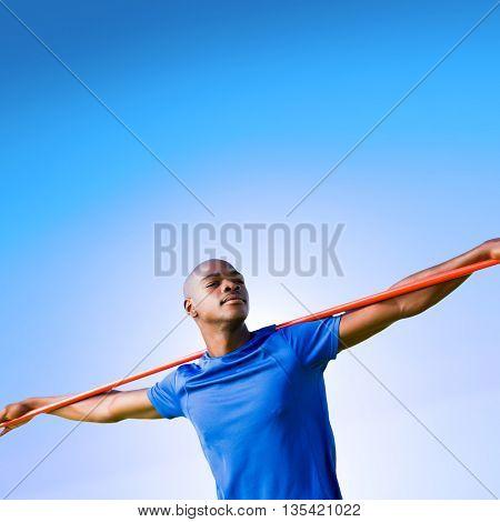 Sportsman with closed eyes preparing to javelin throw against blue sky