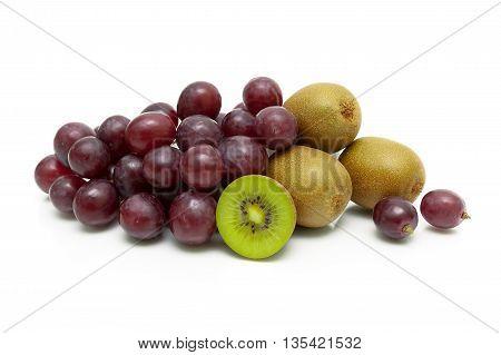 ripe kiwi and dark grapes on a white background. horizontal photo.