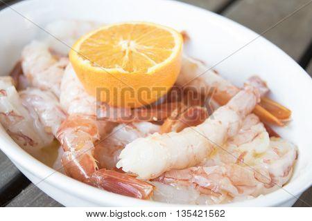 fresh and raw king prawns with orange sauce