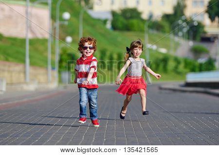 photo of two happy children running on the promenade