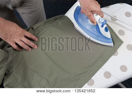 Hands Of Man Ironing Clothes On Ironing Board