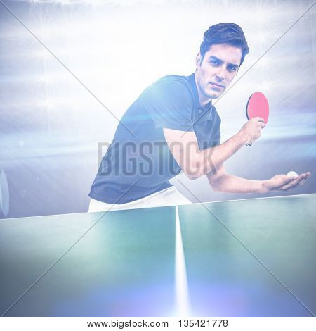 Confident male athlete playing table tennis against american football arena