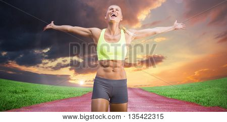Fit woman celebrating victory with arms stretched against view of an empty street