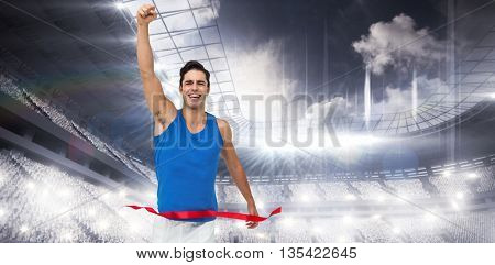 Portrait of cheerful winner athlete crossing finish line against sports arena
