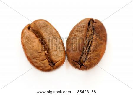 Two coffee beans on white. Macro shot