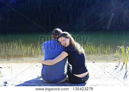 Loving couple hugging on beach. Girl hugging a guy and her head resting on his shoulder. smiling