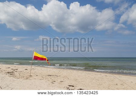 Red and yellow swimming area flag at Tisvilde beach in Denmark.