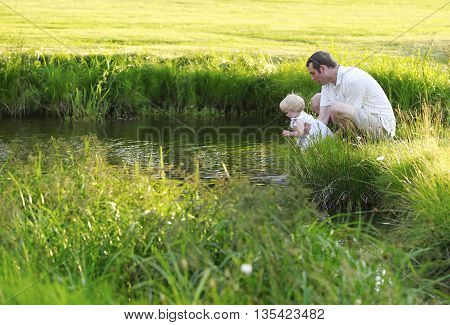 Father Holds The Baby Above Water And Wets Her Feet