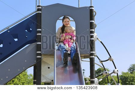 Mother With Her Daughter On Playground. Sunny Day