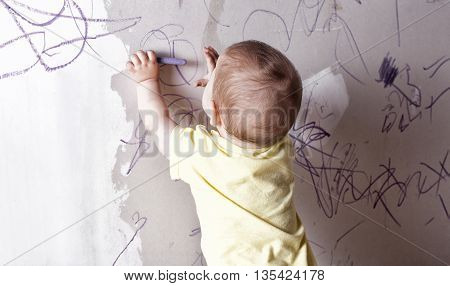 Baby boy drawing with wax crayon on plasterboard wall. He is with his back towards