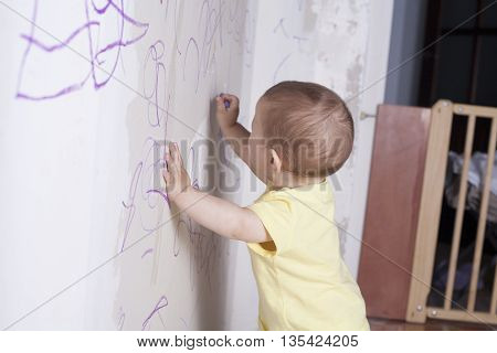 Baby boy drawing with wax crayon on plasterboard wall. We can see a wooden safety gate