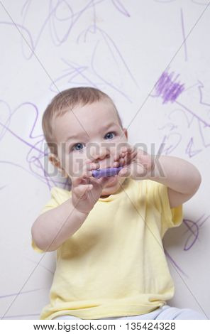 Baby boy with wax crayon on plasterboard wall. He is looking to the camera