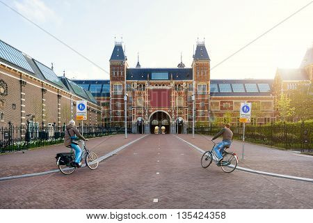 Amsterdam transport in Netherlands - People on bicycles passing by Rijksmuseum in Amsterdam Netherlands. Bicycle is the main transportation in Amsterdam Netherlands.