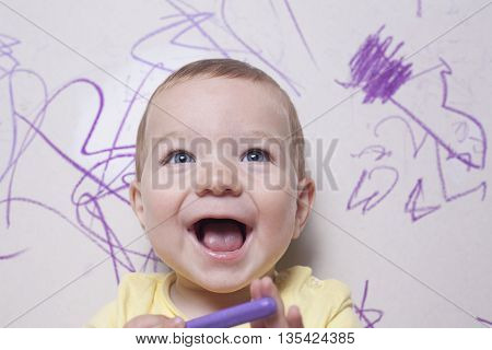 Smilling baby boy with wax crayon. He is looking to the camera