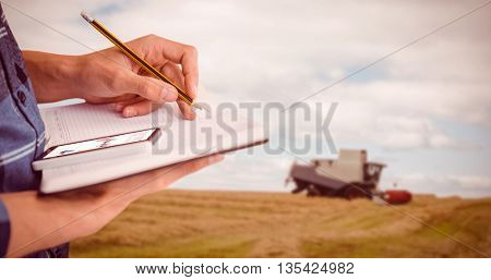 Cropped image of businessman writing with pencil on book against view of a harvester on a field