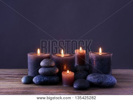 Spa stones with burning candles on grey background