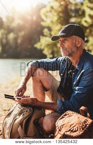 Senior Hiker Sitting By A Lake On Summer Day