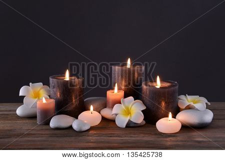 Spa stones with burning candles and flowers on grey background