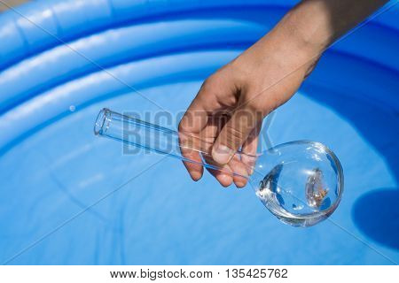 Water testing at swimming pool, laboratory glassware in hand
