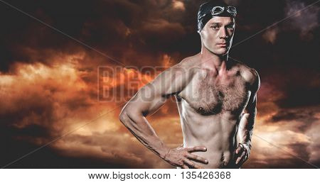Swimmer standing with hand on hip against aerial view of a city on a cloudy day