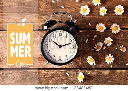 Vintage clock and daisy flowers with text Summer time on wooden background