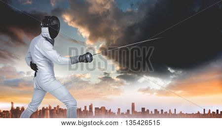 Man wearing fencing suit practicing with sword against city on the horizon