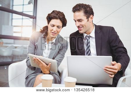 Business people with technology while discussing at office