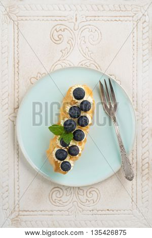 Eclair with buttercream and  blueberries on a plate