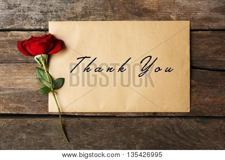 Card with text Thank You and beautiful rose on wooden background